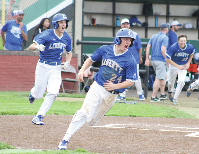 Liberty's Mitchell Okuley (24) leads his teammates toward Brennan Rowe, who was waiting in the middle infield after singling him home for the game-winning run in Thursday's 5-4 Division I district championship win over Marysville.