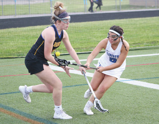 Olentangy's Katie Berberick, left, and Liberty's Jenna Lickovitch battle for possession during the first half of Monday's Division I, Region 1 tournament game in Powell.