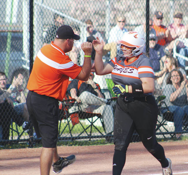 Hayes' Liaiha Slayton high fives head coach Mark Thomas as she heads for home after hitting a homer in the third inning of Tuesday's OCC showdown against visiting Hilliard Darby.