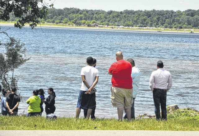 Over a dozen people gathered on Monday around 1 p.m. near the Alum Creek State Park New Galena boat ramp as rescue crews continued their search for a man who went missing in the waters on Sunday. Pictured in the background are some of the rescue boats searching the waters near Alum Creek State Park Beach.