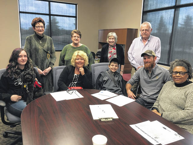 Dr. Jane E. Graebner (standing, second from right) and the DCDA board pose for a photo with last year's Camp Hamwi recipients, Makenzie Levings (sitting, far left) and Gavin Keller (sitting, middle). The DCDA pays for two-thirds of the campers' registration to the camp for diabetic youth.