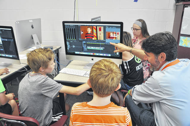 Film instructor Thomas Hering gives a few editing tips to Joshua Callendine and Evan Maus, students who participated in the 2018 Summer Enrichment Academy Friday at Dempsey Middle School.