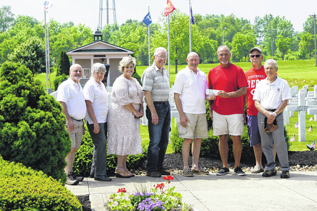 Neal Kruse (red shirt) holds a $5,050 check donation for the Ohio Fallen Heroes Memorial from members of the Sunbury Lions Club on May 31.
