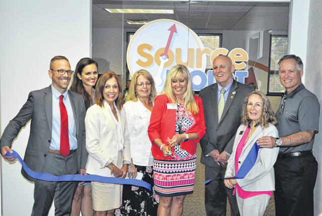 Surrounded by officials from Delaware County, the Westerville Area Chamber of Commerce and SourcePoint, Fara Waugh, director of client services at SourcePoint, cuts the ribbon during a ceremony held Tuesday at the new SourcePoint South Office, 1070 Polaris Parkway, Suite 200.,