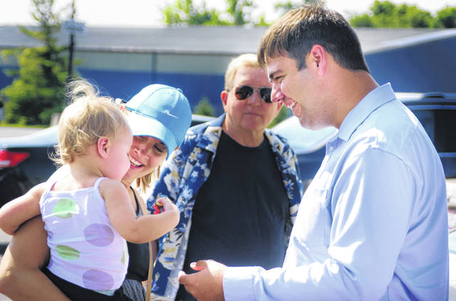Evelyn McWilliams, being held by her mother Danielle, seemed a little shy to meet with 12th Congressional District Democratic candidate Danny O'Connor Tuesday morning as he met with the district's constituents in the parking lot of the Frank B. Willis Government Center as early voting got underway for the Aug. 7 special election.