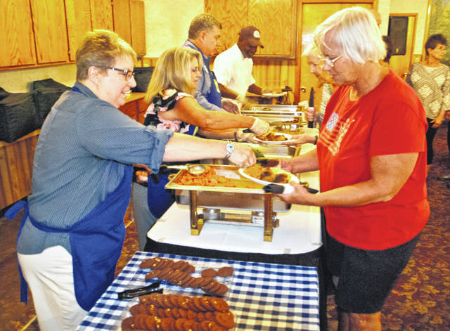 During a grand opening celebration held Thursday at the White Lily Chapel in Ashley, more than 50 older adults gathered for food, music and games. Nutritionist Karen Pillion, left, of SourcePoint, who designed the menu for the event, serves Amy Runyan, right, a cookie.