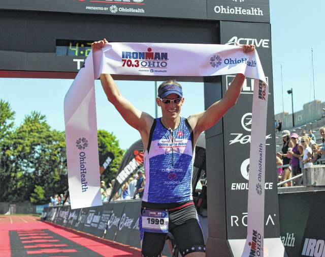 Buffalo resident Jonathan Bottoms celebrates after crossing the finish line inside Selby Stadium during last year's IRONMAN 70.3 Ohio.
