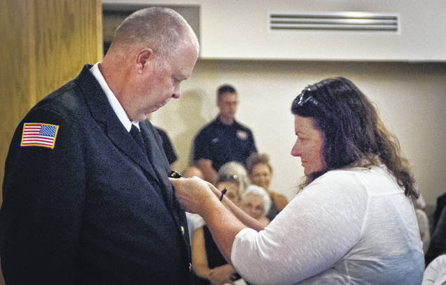 """Before her husband, Clyde """"Butch"""" Vanhoose, was sworn-in as Orange Township's fire inspector, Catherine VanHoose pinned his badge to his dress uniform jacket."""