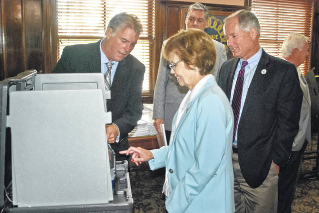 In a special work session held Aug. 20, the Delaware County Board of Elections and county commissioners discussed the options of an electronic voting machine versus using paper ballots. Jay Perbix (left), RBM Consulting election consultant, shows Commissioner Barb Lewis (middle) the ease the touchscreen offers in selecting candidates and issues on election day, while Commissioner Jeff Benton (right) closely watches the demonstration.