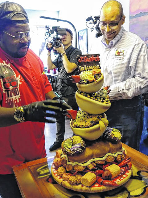 "A camera crew working on an episode of Food Network's ""Ridiculous Cakes"" films the unveiling of the cake made in recognition of the sixth anniversary of the opening of J. Gumbo's Delaware. Pictured in the downtown Delaware restaurant are Tim ""Timbo"" Sullivan (left), who made the cake, and restaurant owner Richard Upton (right)."