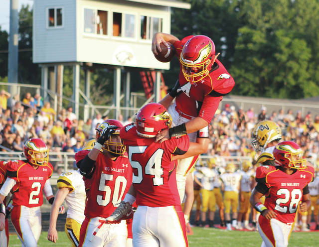 Big Walnut's Nathan Lawyer (4) is congratulated by teammates Wes Coey (54) and Josh Hageman (50) after scoring a touchdown in the first quarter of Friday's non-league showdown against visiting Buckeye Valley.