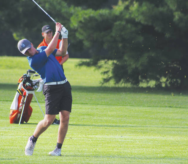 With Delaware Hayes' Mark Sulek looking on, Olentangy Berlin's Bryce Reed follows through on an approach shot during Thursday's Fidelity Federal Savings and Loan Mike Nesselroad Invitational at Oakhaven.