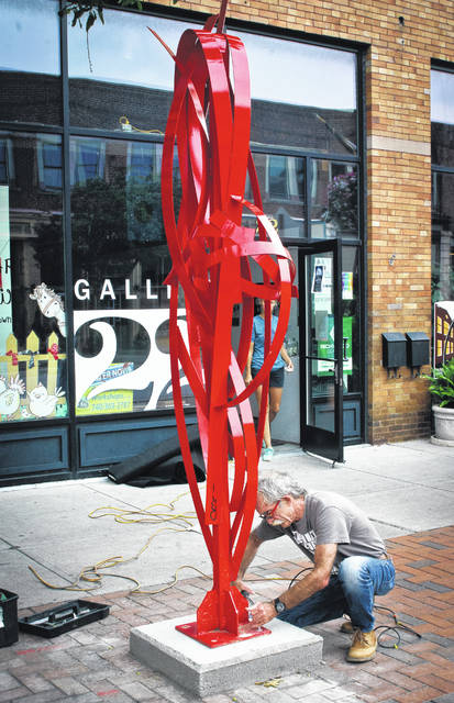 """Hunched over his heavy-duty power drill, award-winning heavy metal sculptor Mac Worthington installs his nearly 10-foot-tall sculpture in front of Gallery 22 in downtown Delaware Friday afternoon. The sculpture, """"A Good Time Then,"""" was unveiled during Main Street Delaware's September First Friday celebration. The sculpture is now on permanent display on East Winter Street."""