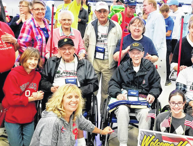 Following the 90th Honor Flight Columbus trip to Washington, D.C. on Sept. 8, the 80-plus veterans who went on the trip were greeted with a welcome home celebration upon their arrival back in Columbus. Pictured surrounded by some of the well-wishers at John Glenn Columbus International Airport are three Delaware veterans (left to right): Bill Warner (black coat), a Marine Corps veteran; Bob Rietz (standing, tan coat), an Army veteran; and Lee Siegwald (black coat), an Army veteran.