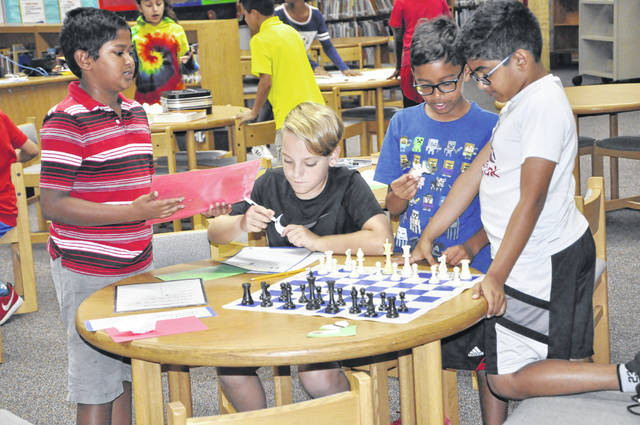 From left to right: Rishit Pendota, Caleb Suitor, Ayush Ghosh and Sahil Rao work together at the chess board station during the Key to Kindness exercise at Glen Oak Elementary School in Lewis Center on Tuesday.