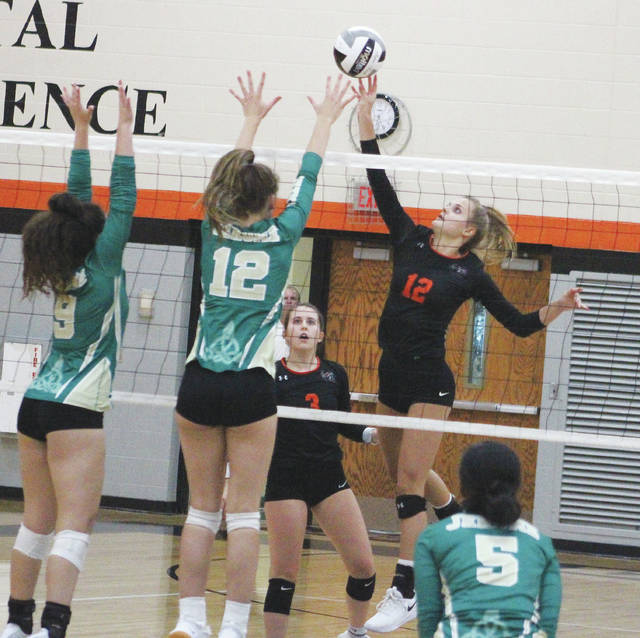 Hayes' Hadlee Bruns, right, lofts a shot over Dublin Jerome's Kendall Poach, middle, and Lauren Gilbert during the first set of Thursday's OCC showdown in Delaware.