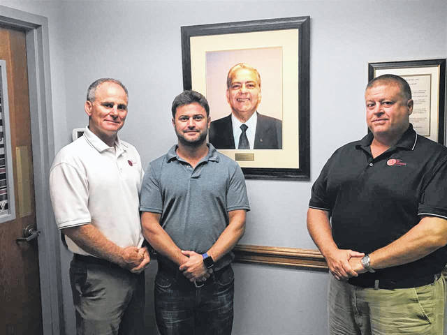 From left to right: Brian, Sean and Rod Meade stand in front of a picture of their father and grandfather, Russ Meade, who founded Meade and Associates in 1978. The company recently celebrated its 40th anniversary.