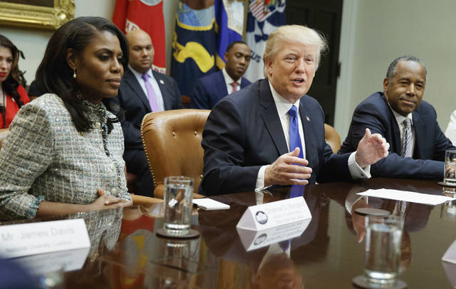 "FILE - In this Feb. 1, 2017, file photo, President Donald Trump speaks during a meeting on African American History Month in the Roosevelt Room of the White House in Washington. From left are, Omarosa Manigault, Trump, and then-Housing and Urban Development Secretary-designate Ben Carson. Omarosa Manigault Newman — the former ""Apprentice"" contestant who became one of Trump's most prominent African -American supporters — has resigned from the White House.(AP Photo/Evan Vucci, File)"