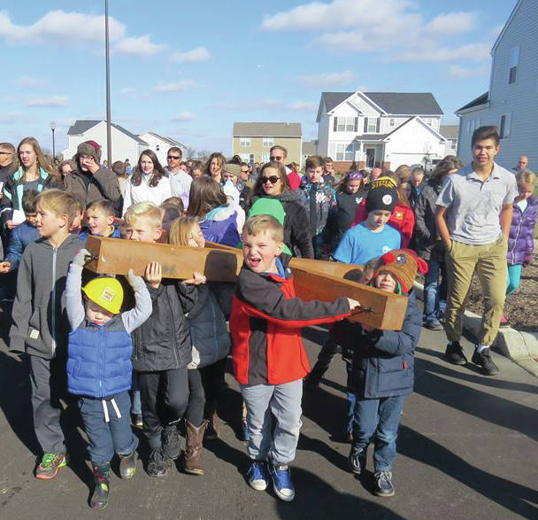 "On Nov. 26, members of Sunbury Christian Church carried a cross 1.8 miles from its old location on Rainbow Avenue to its new location on Admiral Drive. The ""generational journey"" had children carrying the cross the final steps of the way."