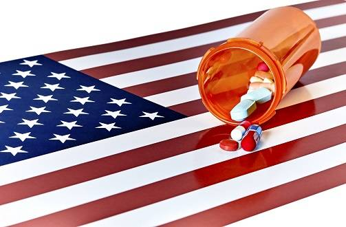Prescription Medications laying on an American Flag isolated on white