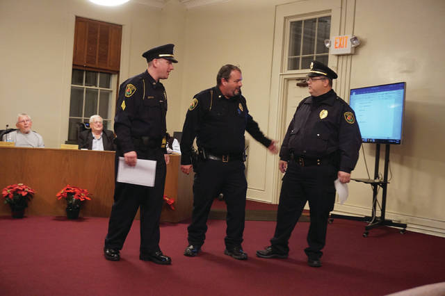 Sunbury Police Officers Chris Meacham, left, and Craig Landis, right, are congratulated by Chief Robert Howard after being promoted at the Village Council meeting on Dec. 6.