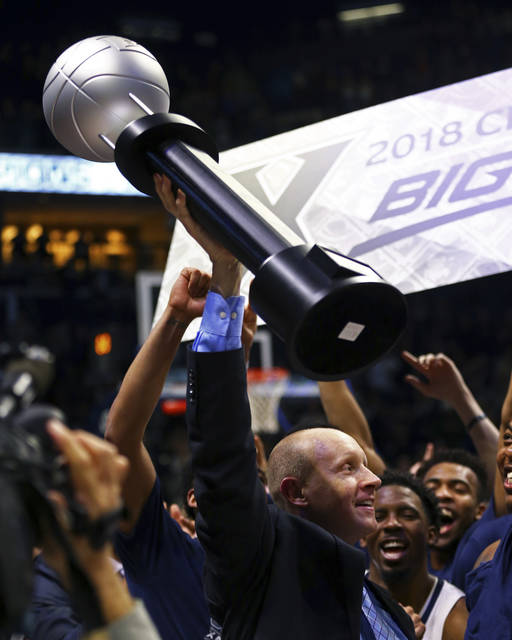Xavier's head coach Chris Mack holds up the Big East Trophy after clinching at least a share of its first Big East championship after an NCAA college basketball game against Providence, Wednesday, Feb. 28, 2018, in Cincinnati. Xavier won 84-74. (AP Photo/Aaron Doster)