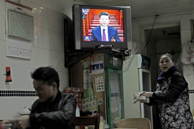 Chinese President Xi Jinping is shown on a news broadcast of the opening session of the National People's Congress in a restaurant in Shanghai, China, Monday, March 5, 2018. (AP Photo)