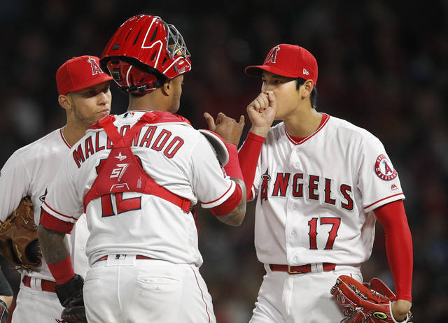 Los Angeles Angels starting pitcher Shohei Ohtani, right, of Japan, and Andrelton Simmons, left, listen to catcher Martin Maldonado during the second inning of a baseball game against the Boston Red Sox, Tuesday, April 17, 2018, in Anaheim, Calif. (AP Photo/Jae C. Hong)