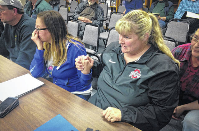 As Harlem Township trustees voted Tuesday on a rezoning measure, opponents to the measure, Brittany Bowers, left, and Susi Perry, right, hold a tight grip on each other's hand as they await the outcome of the the vote.