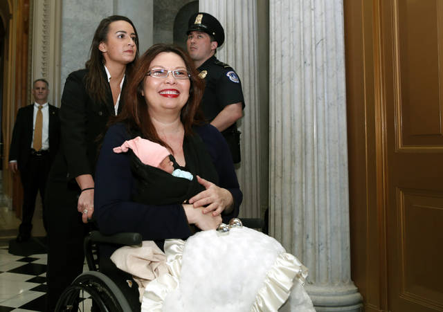 Sen. Tammy Duckworth, D-Ill., carries her baby Maile Pearl Bowlsbey after they went to the Senate floor to vote, on Capitol Hill, Thursday, April 19, 2018 in Washington. (AP Photo/Alex Brandon)