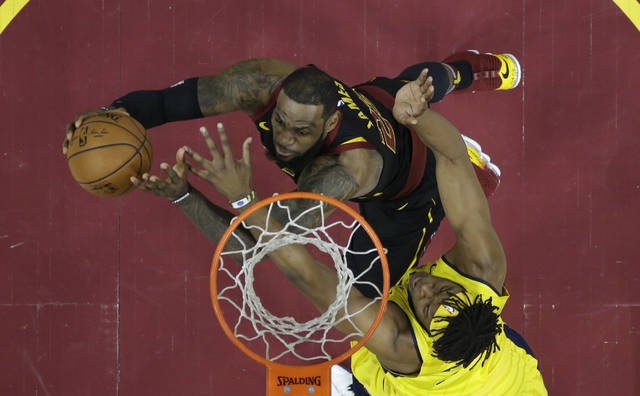 Cleveland Cavaliers' LeBron James, left, drives to the basket against Indiana Pacers' Myles Turner in the first half of Game 7 of an NBA basketball first-round playoff series, Sunday, April 29, 2018, in Cleveland. The Cavaliers won 105-101. (AP Photo/Tony Dejak)