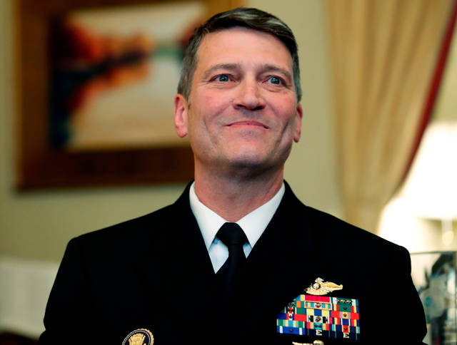 FILE - In this April 16, 2018, file photo, U.S. Navy Rear Adm. Ronny Jackson, M.D., sits before a meeting on Capitol Hill in Washington. Jackson, who abandoned his nomination to be secretary of Veterans Affairs amid numerous allegations, will not return to the job of President Donald Trump's personal physician but will remain on the White House medical staff, Politico reported Sunday, April 29. (AP Photo/Alex Brandon, File)