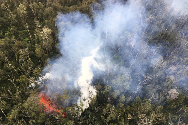 In this May 7, 2018 photo provided by the U.S. Geological Survey, smoke rises from a fissure in Leilani Estates in Pahoa, Hawaii. Hawaii's erupting Kilauea volcano has destroyed homes and forced the evacuations of more than a thousand people. (U.S. Geological Survey via AP)