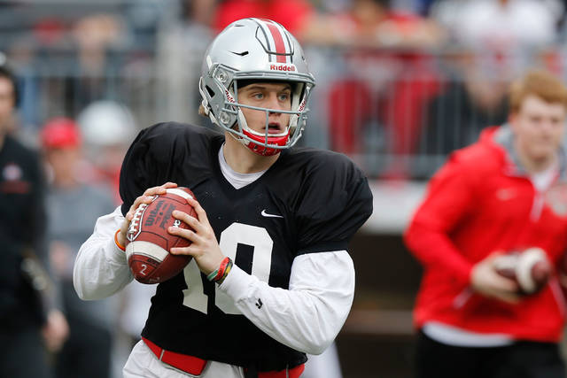 FILE - In this April 14, 2018, file photo, Ohio State quarterback Joe Burrow drops back to pass during an NCAA college spring football game in Columbus, Ohio. Facing the possibility of sitting as a backup for a third season at Ohio State, quarterback Joe Burrow announced on Tuesday, May 8, 2018,  his intention to transfer. The news from the redshirt junior, delivered via Twitter, wasn't unexpected.  (AP Photo/Jay LaPrete, File)