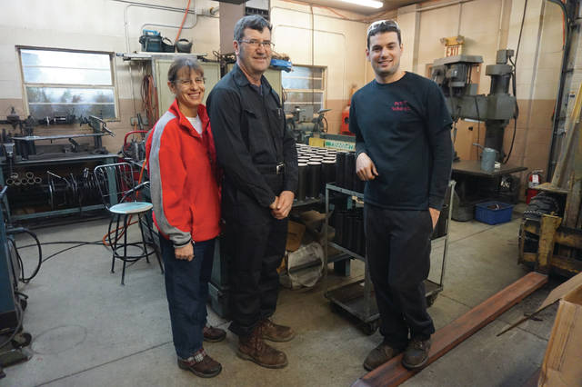 The Harp family — Beth, Rodney and Kurtis — stand by a machine in their Sunbury shop. A finished product, a can-trimmer, used by companies for quality inspection.