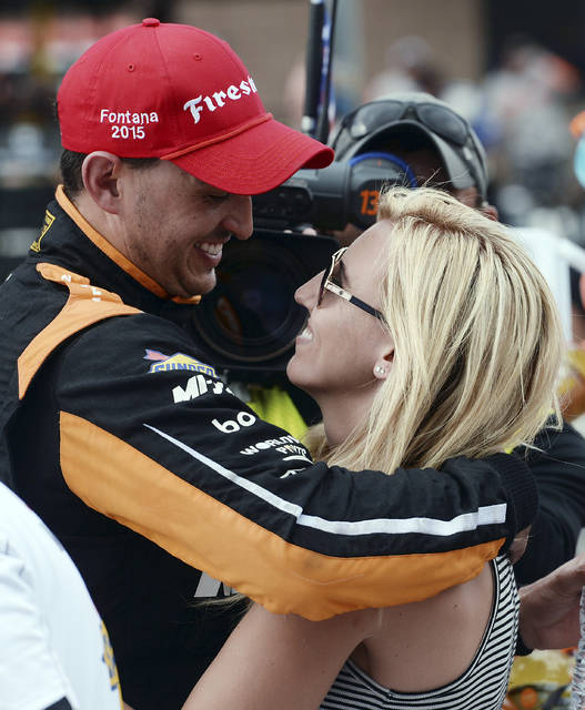 FILE - In this June 27, 2015, file photo, Graham Rahal (15) celebrates with his then-fiancee, NHRA Funny Car driver Courtney Force, after winning the IndyCar auto race at Auto Club Speedway in Fontana, Calif. Courtney Force has had a whirlwind few weeks, spending time in Nashville as a presenter at the CMT Music Awards, watching her husband Graham Rahal finish in the top 10 at the Indianapolis 500 and squeezing in sponsor events in places like Chicago and Florida. (AP Photo/Will Lester, File)