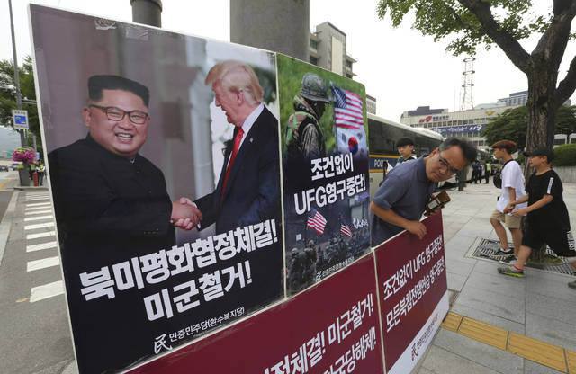 "A photo showing U.S. President Donald Trump and North Korean leader Kim Jong Un is displayed as a member of People's Democratic Party stands to oppose military exercises between the United States and South Korea near the U.S. embassy in Seoul, South Korea, Tuesday, June 19, 2018. The Pentagon on Monday, June 18, 2018, formally suspended a major military exercise planned for August with South Korea, a much-anticipated move stemming from Trump's nuclear summit with Kim. The signs read: "" Stop Ulchi Freedom Guardian (UFG) exercises and withdrawal of U.S. troops."" (AP Photo/Ahn Young-joon)"