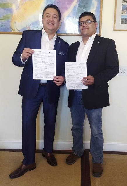 In this Tuesday, June 26, 2018 photo provided by David Quiroa, father David Quiroa, left, and son David Quiroa, Jr., right, hold their candidacy papers in Newport, R.I. The father will run as a Republican and the son will run as an independent in the November general election for the seat currently held by Democratic Rhode Island State Rep. Marvin Abney. (Salome Quiroa via AP)
