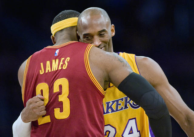 "FILE - In this Jan. 15, 2015, file photo, Los Angeles Lakers guard Kobe Bryant, right, and Cleveland Cavaliers forward LeBron James hug before the start of an NBA basketball game, in Los Angeles. The Los Angeles Lakers have a new superstar — L.A.-Bron. The four-time NBA MVP announced Sunday night, July 1, 2018, that he has agreed to a four-year, $154 million contract with the Lakers. ""Welcome to the family (at)KingJames,"" Bryant said on Twitter . ""(hash)lakers4life (hash)striveforgreatness."" (Paul Rodriguez/The Orange County Register via AP, FIle)"