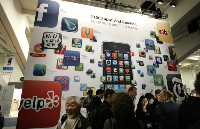 FILE - In this Jan. 6, 2009 file photo, a poster touting applications available for Apple's iPhone and iPod touch is seen at the Macworld Conference and Expo in San Francisco. Since its debut 10 years ago Tuesday, July 10, 2018, Apple's app store has unleashed new ways for us to work, play, and become lost in our screens. (AP Photo/Paul Sakuma, File)
