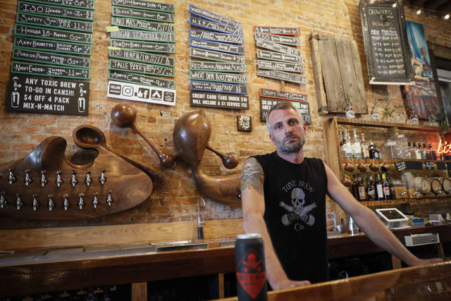 Shane Juhl, owner and proprietor of Toxic Brew Co., poses for a photograph at his taproom located in the Oregon District, Tuesday, July 17, 2018, in Dayton, Ohio. After experiencing its best days in the first half of the 20th century, Dayton is reinventing itself with impressive results. Minor-league baseball, a riverside park and a cluster of craft beer pubs are helping revitalize a downtown that had become frayed around the edges. (AP Photo/John Minchillo)
