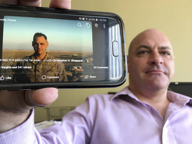 "In this photograph taken July 17, 2018, Marine Corps veteran Chris Sheppard poses with a picture of himself taken during his service in Iraq in Oct. 2004, at his office in Seattle. ""I thought that press conference yesterday with him in Putin, I thought that was a national tragedy. I just couldn't believe it,"" Sheppard said from his office in downtown Seattle. (AP Photo/Manuel Valdes)"