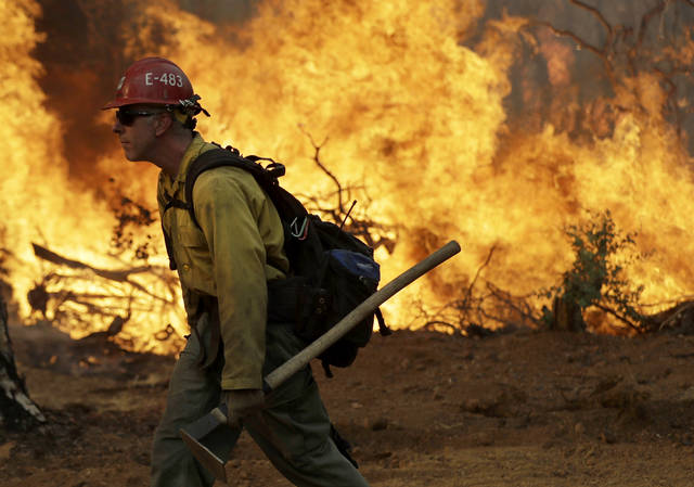 A firefighter walks along a containment line in front of an advancing wildfire Saturday, July 28, 2018, in Redding, Calif. (AP Photo/Marcio Jose Sanchez)