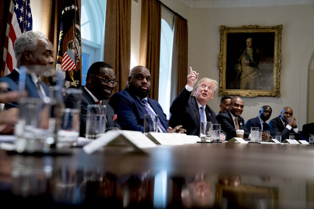 President Donald Trump points up to heaven as he speaks during a meeting with inner city pastors in the Cabinet Room of the White House in Washington, Wednesday, Aug. 1, 2018. (AP Photo/Andrew Harnik)