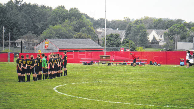 The Boys Junior Varsity Soccer team stands during the playing of the National Anthem before the start of its game against New Albany at Big Walnut High School on Aug. 18. Everyone in the bleachers, the opposing team, and on the sidelines stood, too.