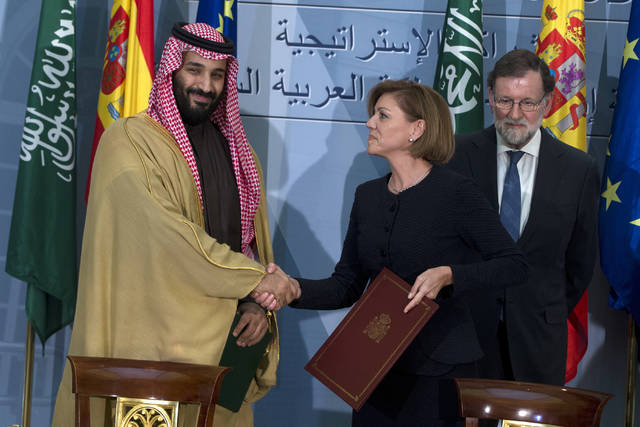 FILE - In this April 12, 2018 file photo, Saudi Arabia Crown Prince Mohammed bin Salman, left and Spain's then Defense Minister Maria Dolores Cospedal shake hands after signing bi-lateral agreements in the presence of the then Prime Minister of Spain Mariano Rajoy, right, at the Moncloa Palace in Madrid, Spain. Spain has cancelled the sale of 400 laser-guided bombs to Saudi Arabia it was reported Tuesday Sept. 4, 2018, amid fears that the weapons could be used in the Riyadh-led coalition fighting the Iran-aligned Houthi rebels in Yemen. The deal was originally signed in 2015 under a conservative government, but the new Spanish center-left administration plans to return the 9.2 million euros (10.6 million dollars) already paid by the Saudis. (AP Photo/Paul White, File)